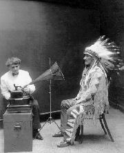 Mountain Chief of the Blackfoot Tribe listens to a cylinder recording of a Blackfoot song made by Frances Densmore (left), 1906. Library of Congress.